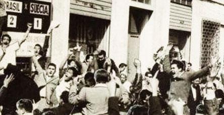 Festejo de gol do Brasil diante de sede de jornal com placar e alto-falante